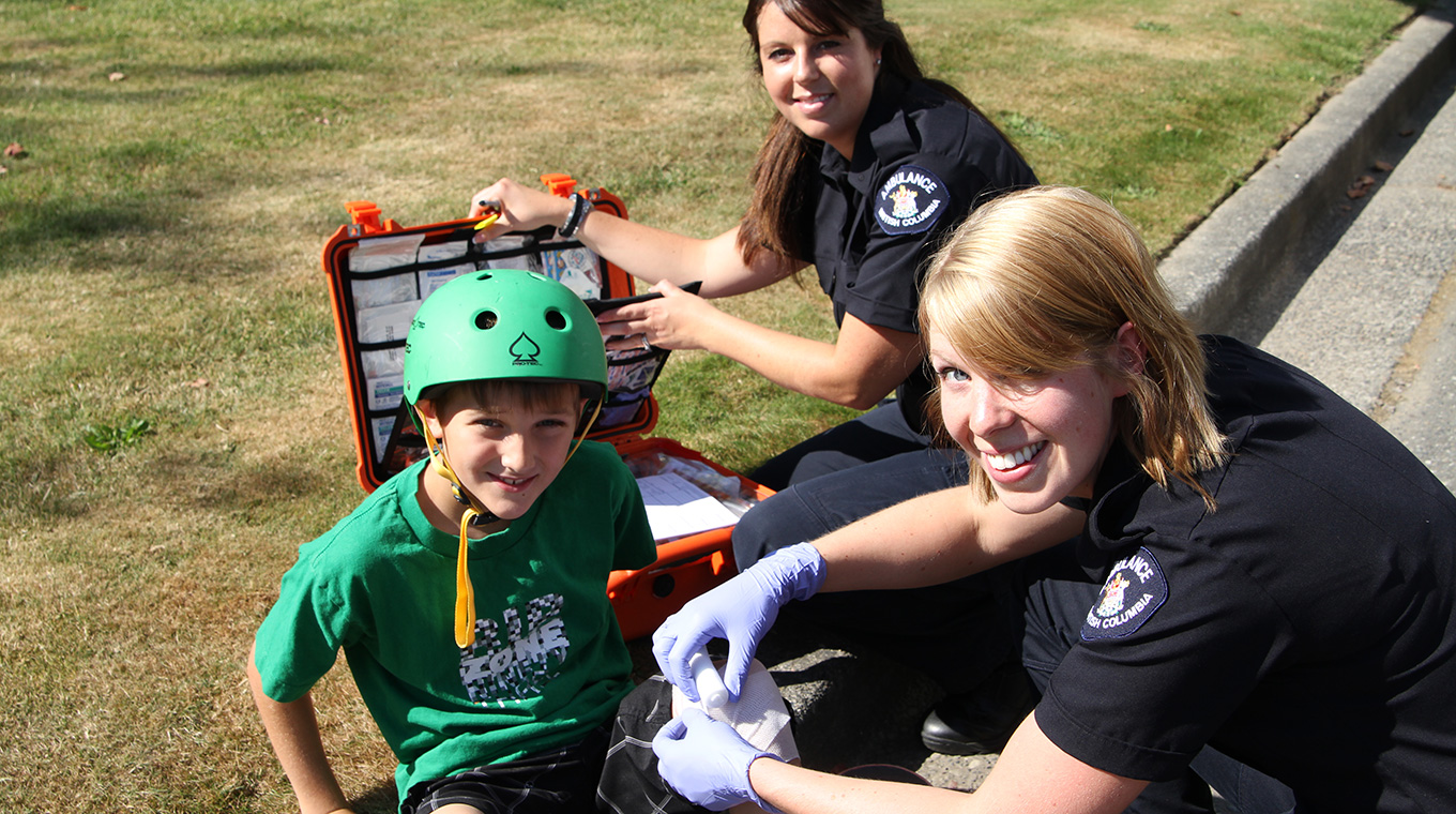 Paramedics treating a child with a skateboarding injury