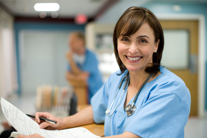 Nurse smiling at camera while filing out paper work