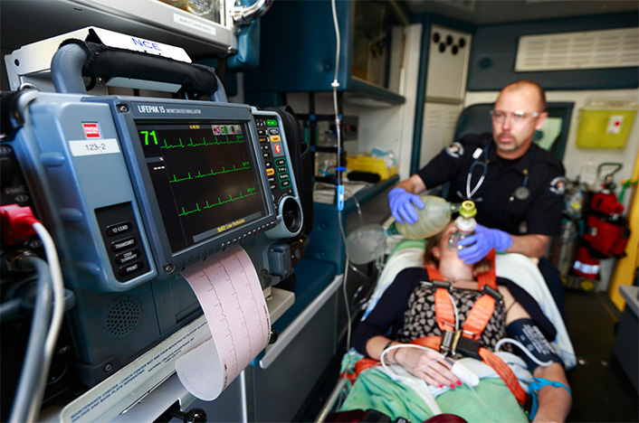 Paramedic treating a patient in the back of an ambulance