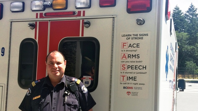 Paramedic stands next to ambulance with ACT FAST stroke awareness decal